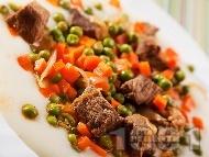 Рецепта Варено / задушено телешко месо с грах, моркови и домати върху канапе от картофено пюре